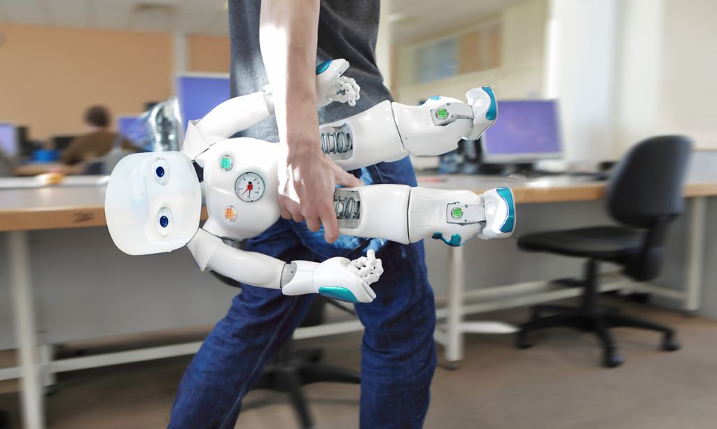AI in customer service: Staff member carries a robot through the office